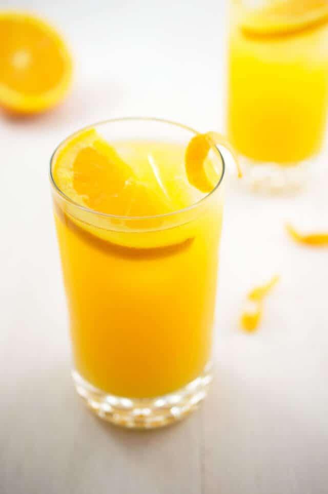 Skinny orange crush with vodka and orange liqueur in a highball glass with orange slice garnish