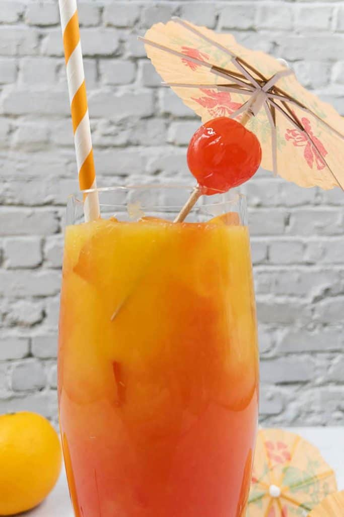 Close up of a great vodka sunrise cocktail with a straw, a maraschino cherry and a cocktail umbrella.