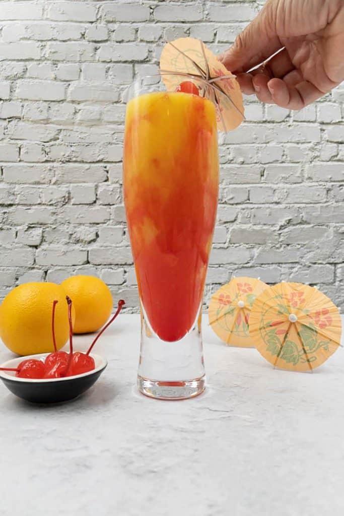 Placing a cherry and umbrella garnish on a vodka sunrise.
