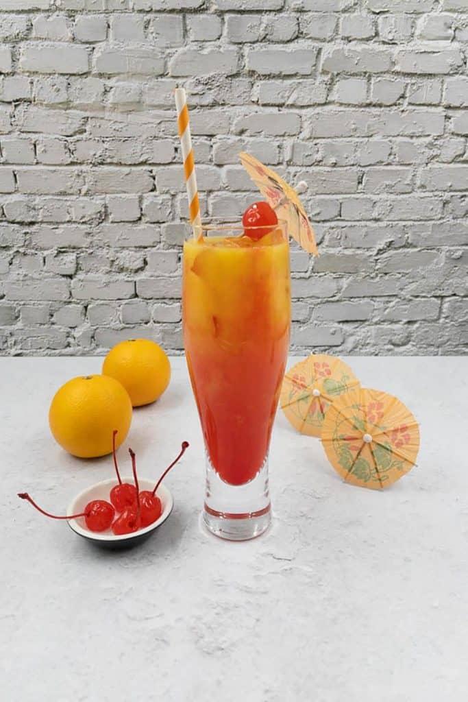 Stunning glass full of vodka sunrise with a cherry and umbrella garnish.