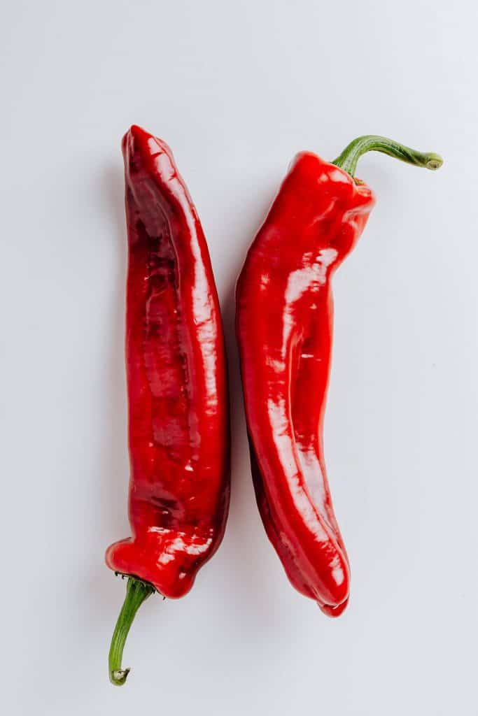 Two fresh red peppers.
