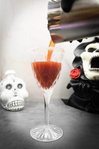 Pouring a cocktail from the crypt Halloween cocktail into a glass with a Calaveras and a monster in the background.