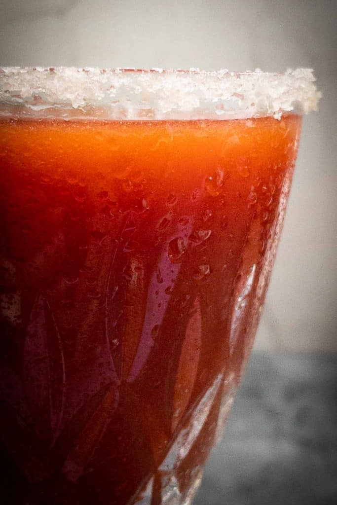 A close up of a blood red Halloween cocktail with a smoked sea salt rim.