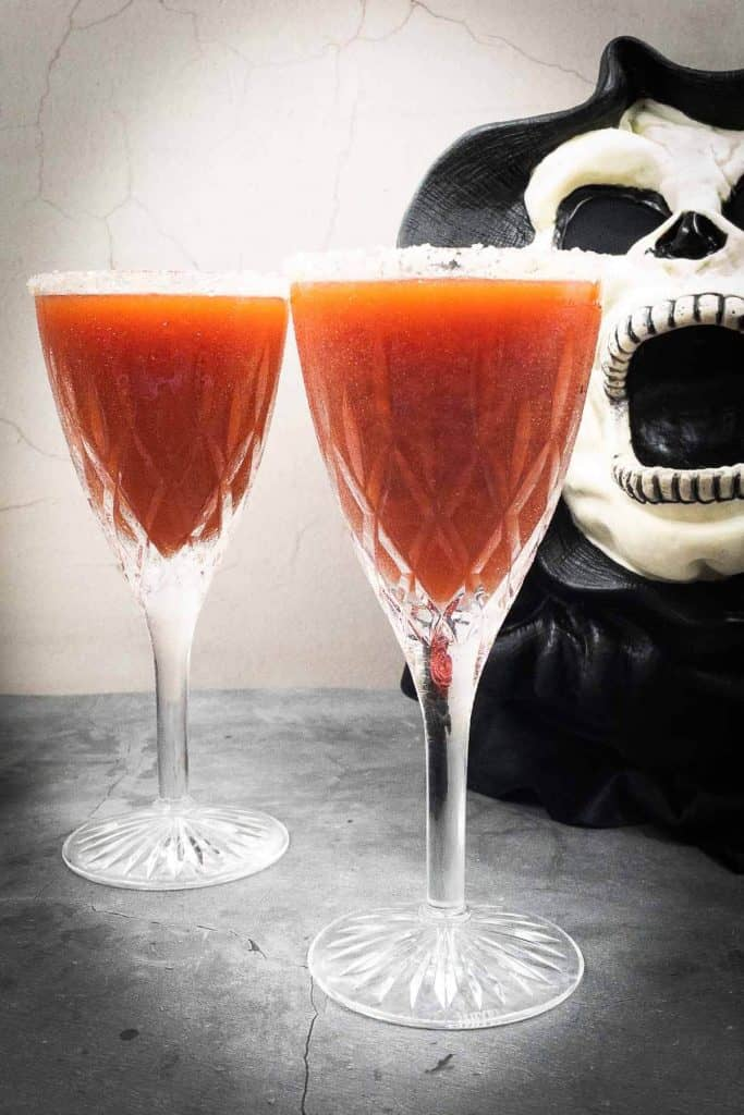 Two blood red Halloween cocktails with a monster in the background.