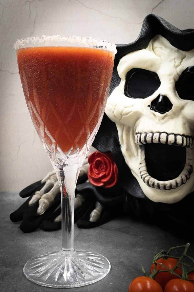 A spooky skeleton about to drink a blood red Halloween cocktail.