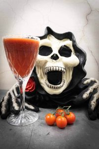 Scary ghoulish monster holding a Halloween cocktail.