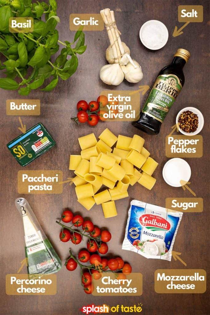 Ingredients for making pasta alla sorrentina, fresh basil, garlic, salt, extra virgin olive oil, pepper flakes, sugar, mozzarella cheese, cherry tomatoes, pecorino cheese, paccheri pasta and butter.