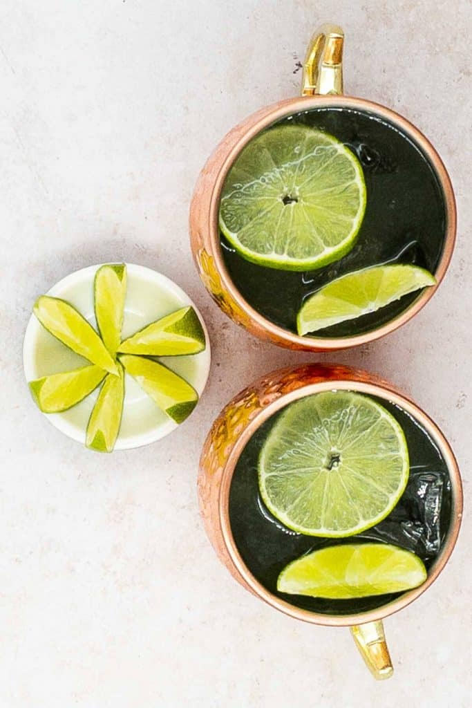 Overhead shot of two mule cocktails, with ice and lime wedge and wheel to garnish.