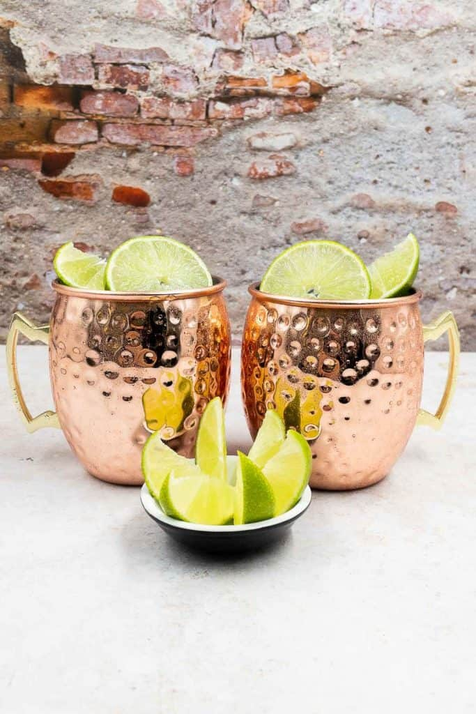 Two Mexican mules, ready to drink in mugs and with garnish of lime wedges and slices.