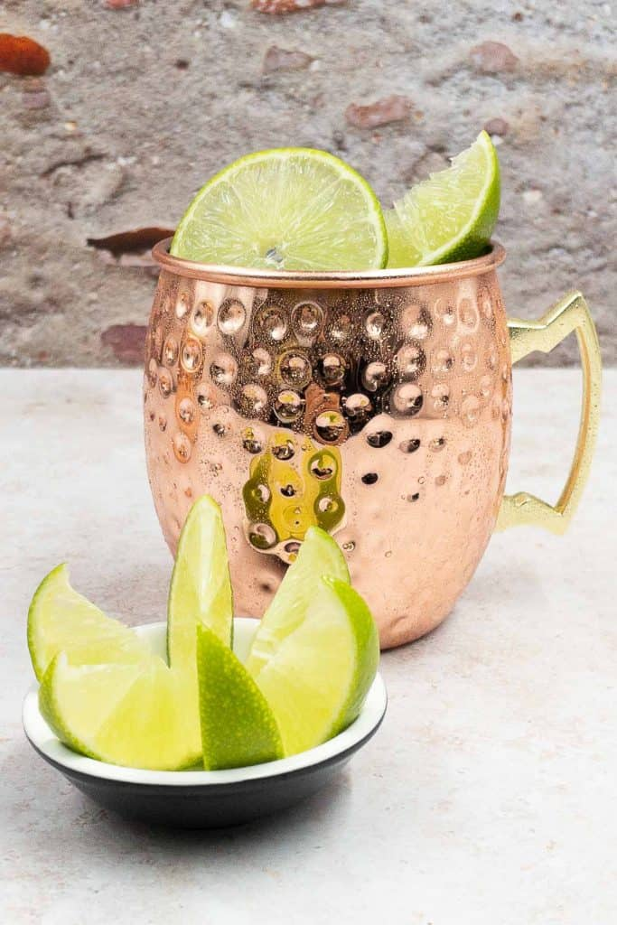 Mule Mexican freshly made with ginger beer and tequila, garnished with lime wedges and wheels.