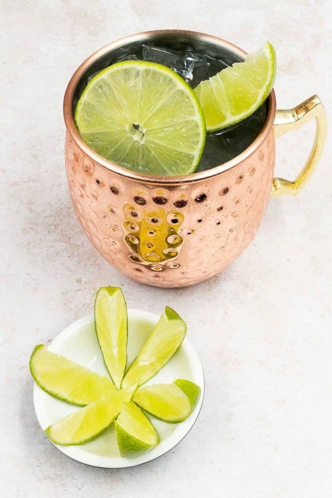 Mule Mexican cocktail in a copper cup, with slices of lime and wedges.