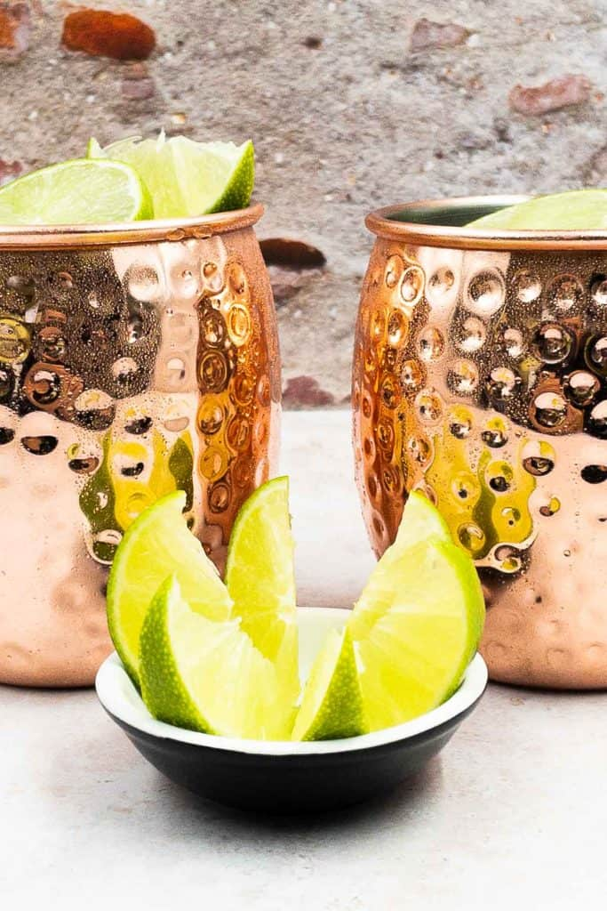 Two spicy mule cocktails, the mules have ice and wedges of lime.