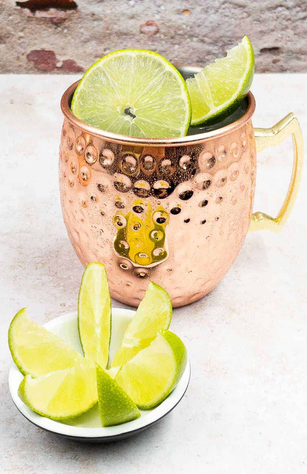 Tasty Mexican Mule Cocktail Drink in a Copper Mug and Slice of lime and wedges.