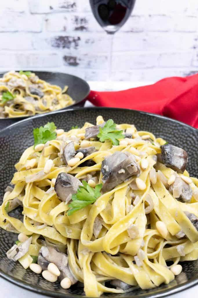 Bowls of mushroom pasta, with mushrooms, pine nuts and fresh parsley in a garlic butter sauce, with a glass of red wine in the background.