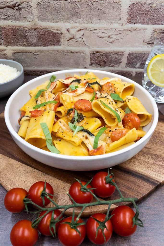 Authentic Italian bowl of pasta alla sorrentina, with fresh tomatoes, chopped basil and mozzarella cheese.
