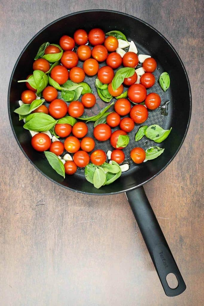 Cherry tomatoes with fresh basil and sliced garlic.