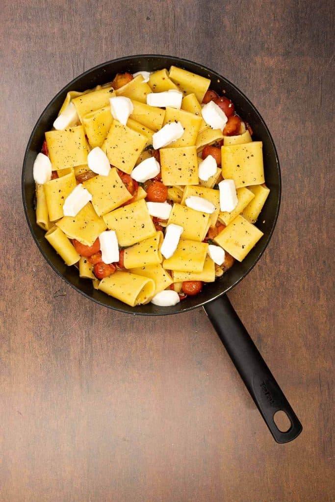Process shot of paccheri pasta with fresh mozzarella and cherry tomatoes.