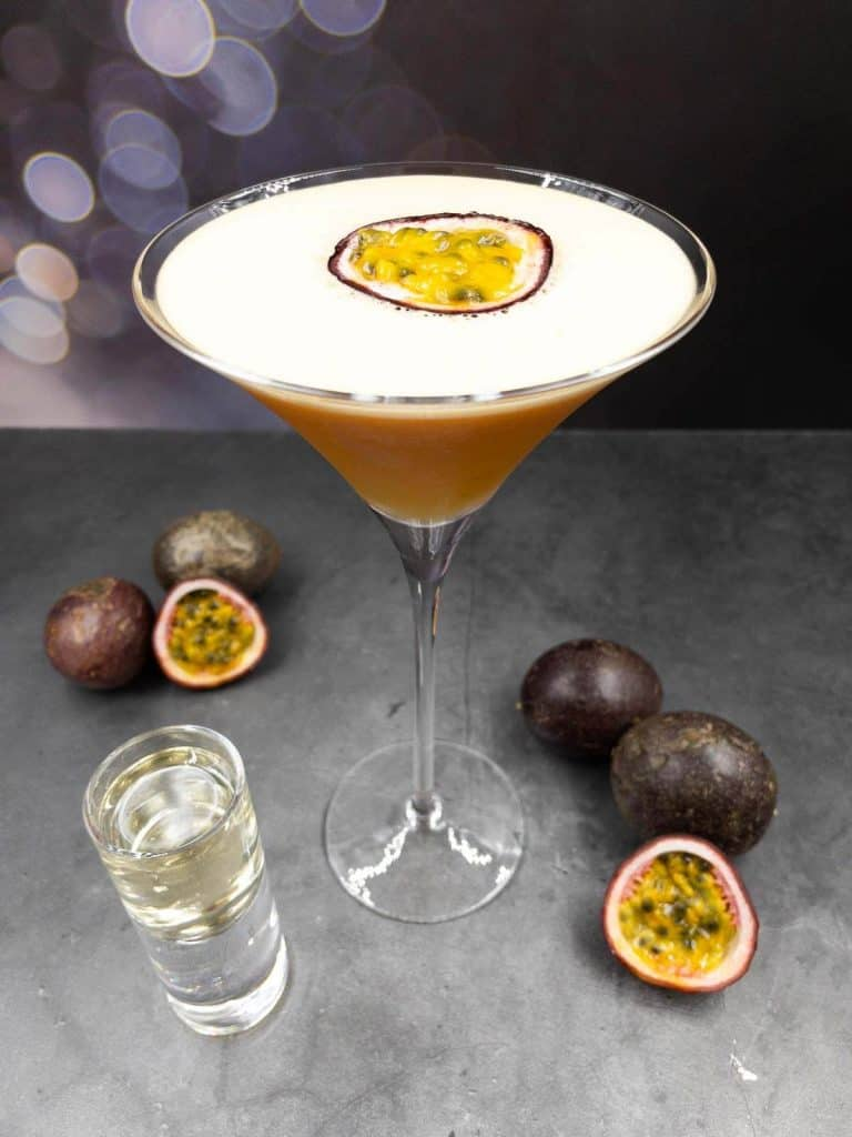 Pornstar martini gin cocktail with a passionfruit garnish, prosecco shot and passionfruit laying around the martini glass.