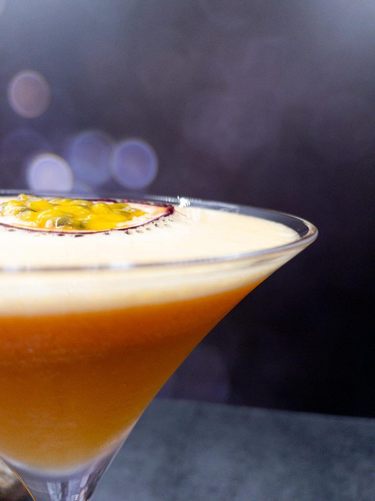 Close up of a homemade pornstar martini gin cocktail with a fresh passionfruit garnish floating on top.