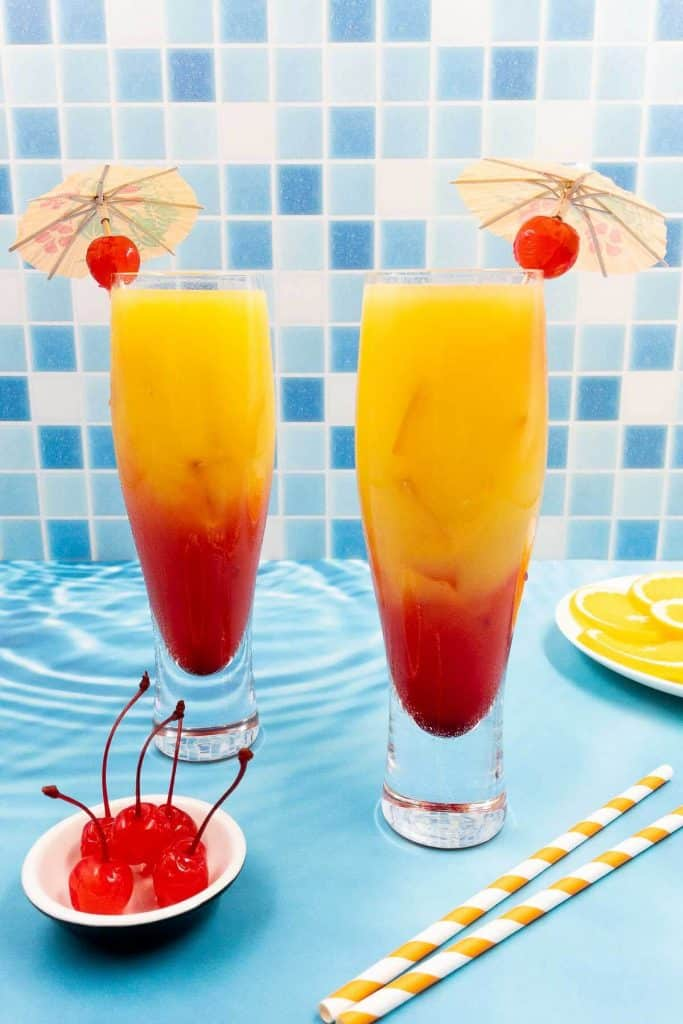 Two tequila sunrise cocktails, both have a cocktail umbrella and a maraschino cherry, two striped straws on the floor, a bowl of maraschino cherries and a plate of orange slices.