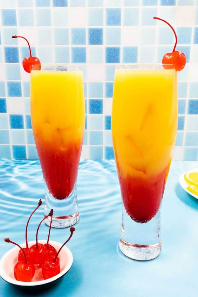 A couple of tequila sunrise cocktails ready to drink, each with a maraschino cherry in, a bowl of maraschino cherries and a slice of orange.