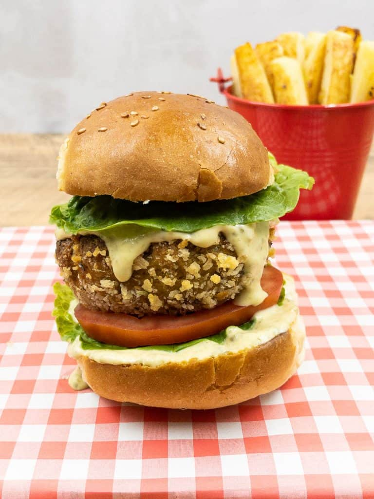 Freshly made vegan plant based chicken burgers ready to eat with an extra crunchy bread crumb coating and a bowl of french fries.
