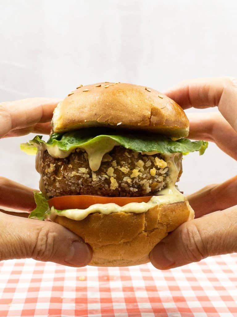 A homemade delicious plant based vegan chicken burger held by two hands.