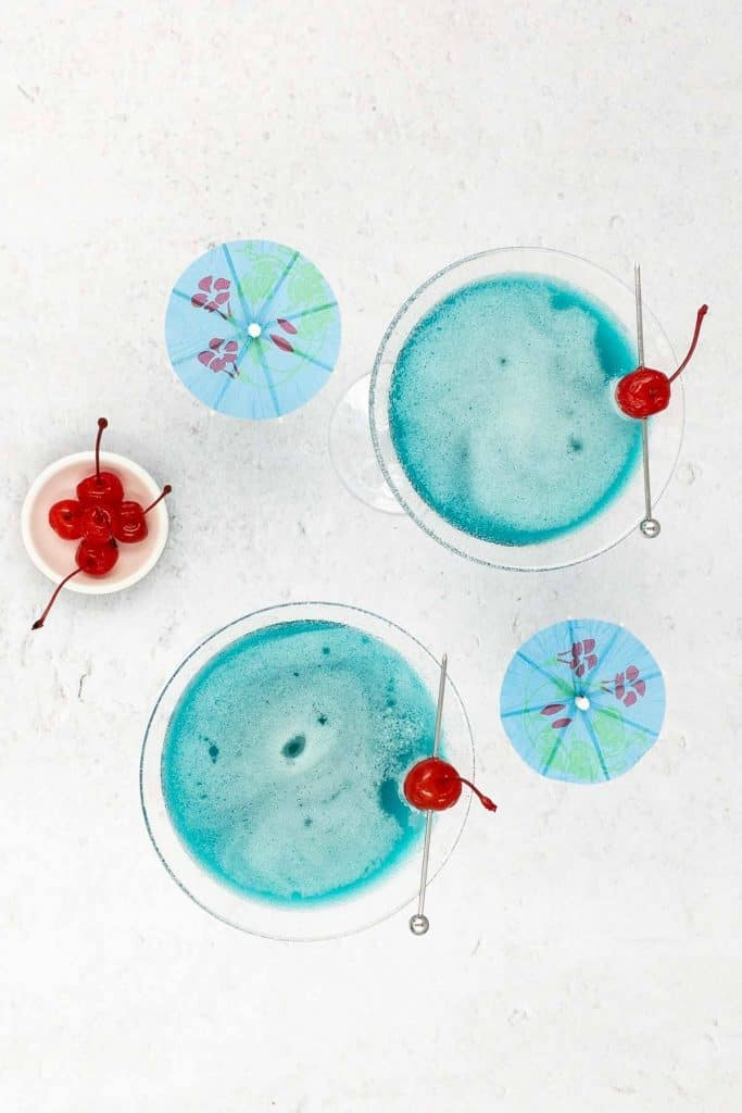 Overhead photo of blue Envy cocktails, with cherries and blue cocktail umbrellas.