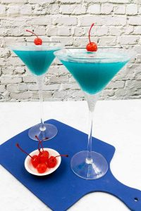 Two blue Envy cocktails on a blue board, both with a garnish of maraschino cherries.