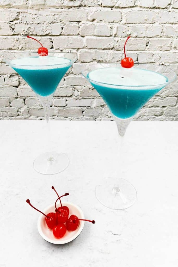 Two bright blue cocktail drinks with red maraschino cherries as garnish.