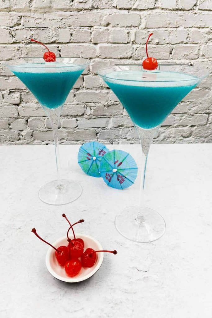Two blue drinks with blue cocktail umbrellas and maraschino cherries.