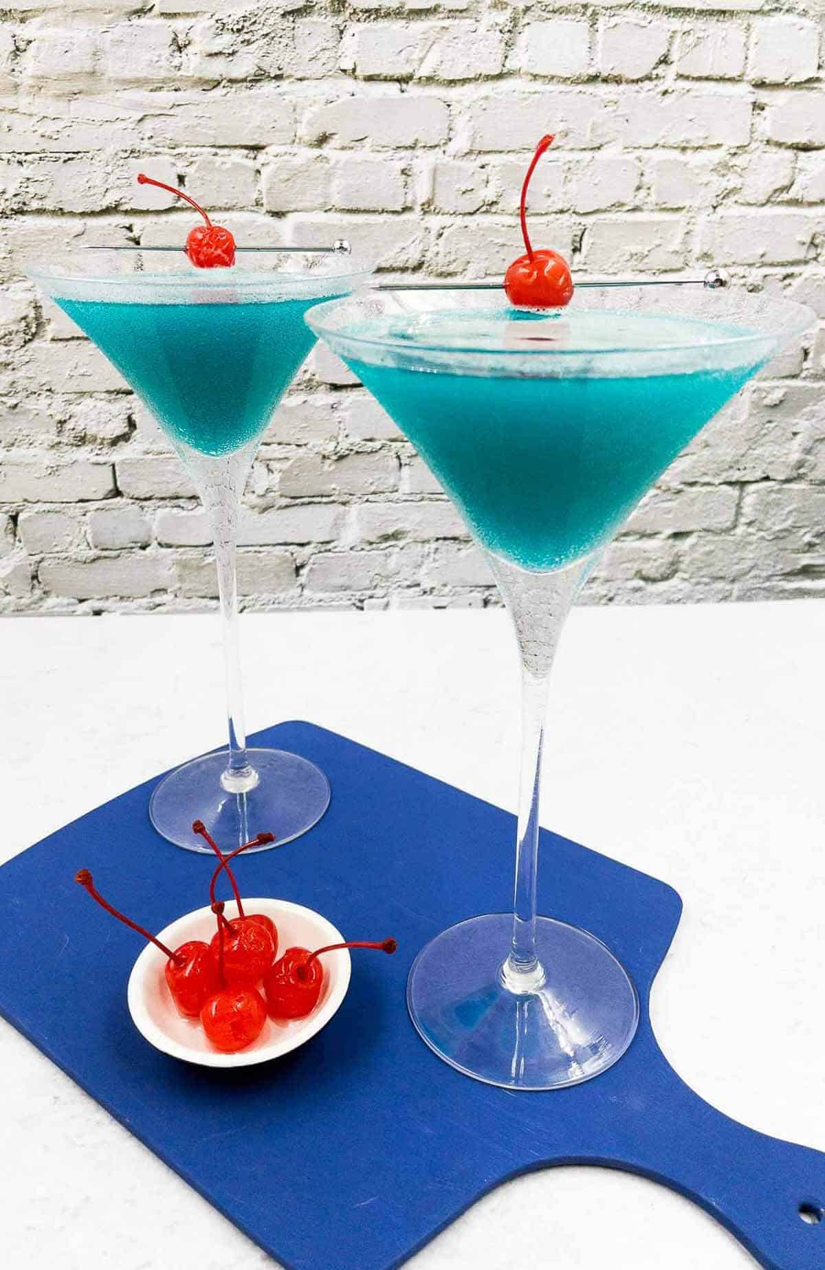 Two Envy cocktails with maraschino cherries.