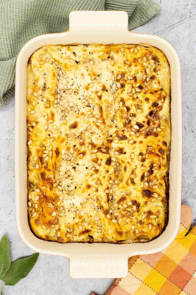 Overhead shot of a delicious four cheese and mushroom lasagna, with pine nuts sprinkled over the top, sage leaves in the corner, an oven glove and tea towel.