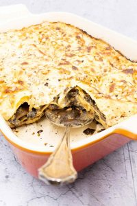 A whole dish of four cheese and mushroom lasagna all cooked and ready to eat.