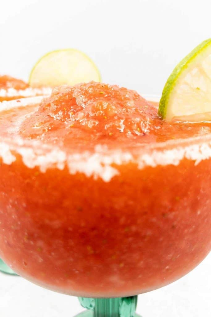 A close up of icy frozen strawberry margaritas with salted rims and lime slices.