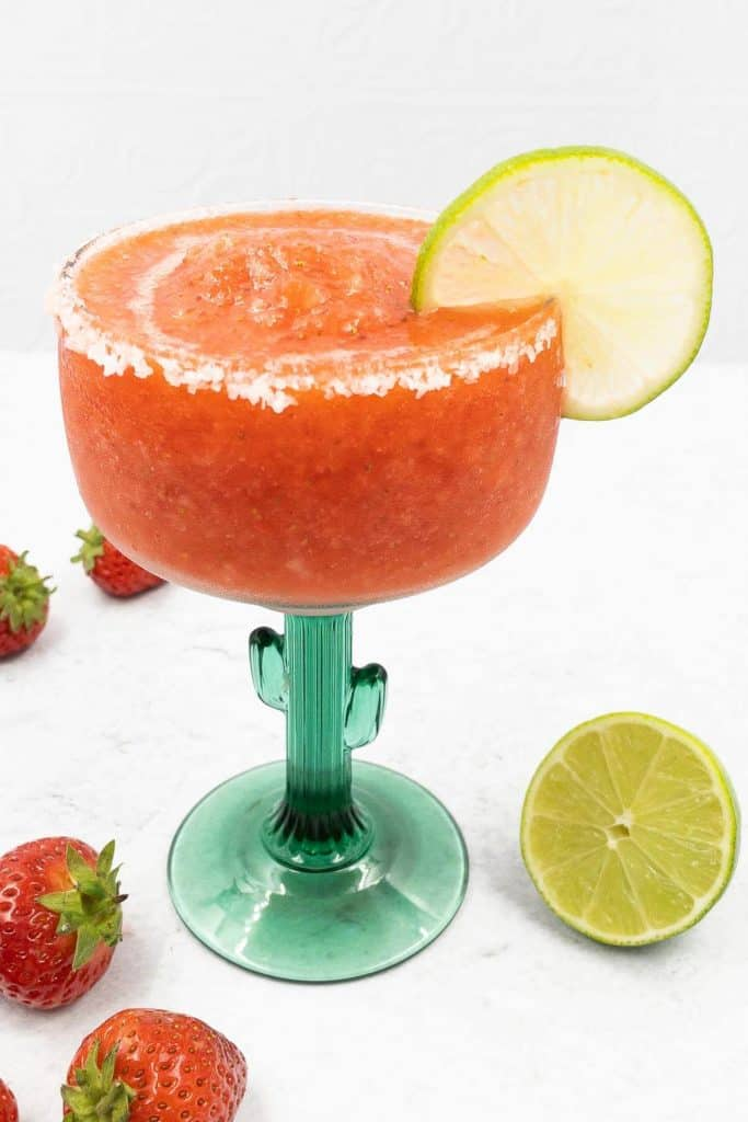 A frozen strawberry margarita made from scratch with a lime wheel garnish.