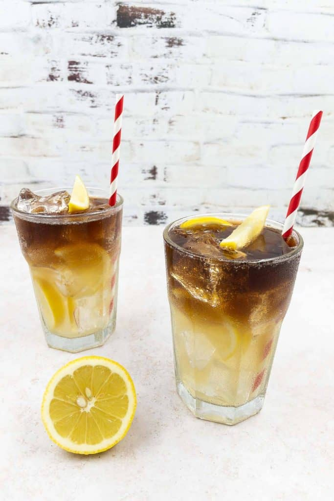 Two Long Island Iced Tea drinks, with tequila, gin, vodka, triple sec orange liqueur, with lemon garnish, straws and served in highball glasses.