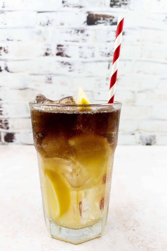 Homemade Long Island Iced Tea in a highball glass, with a straw and lemon garnish, chilled and ready to drink.
