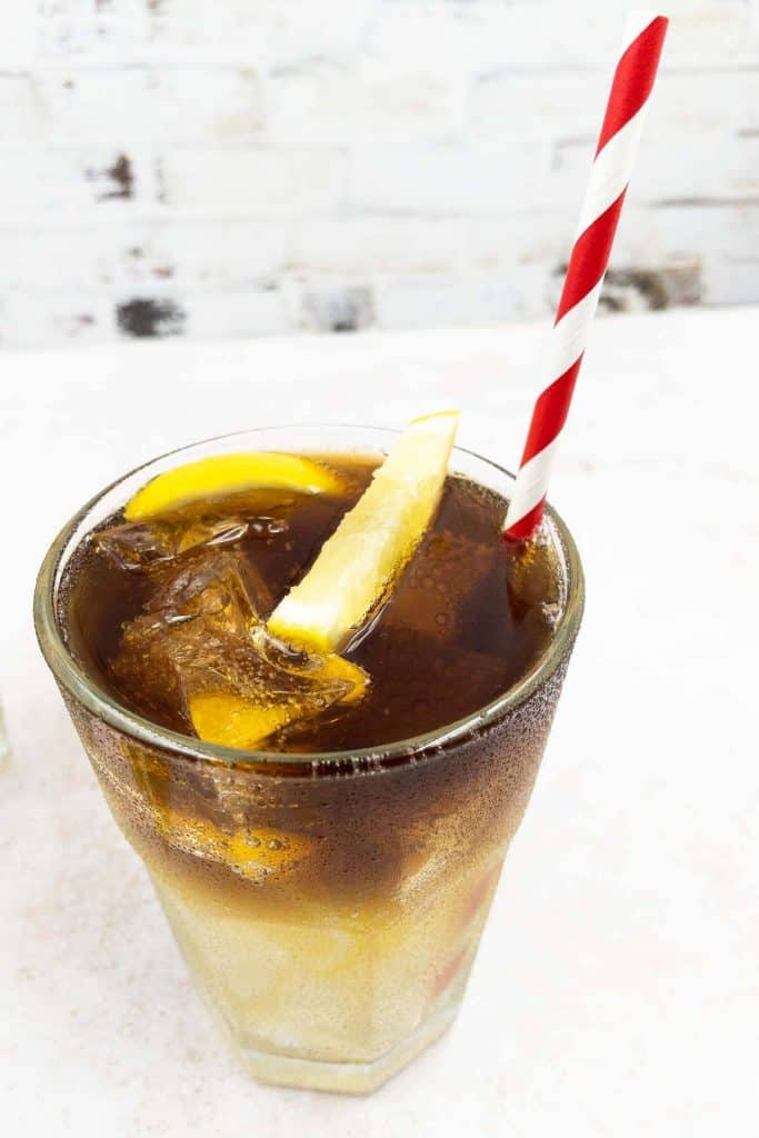 Close up of a Long Island Iced Tea drink, freshly made with tequila, gin, rum, triple sec, vodka, topped with cola and a lemon garnish.