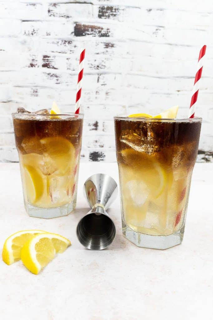 Two glasses of Long Island Iced Tea with a cocktail jigger, lemon slice and straws.
