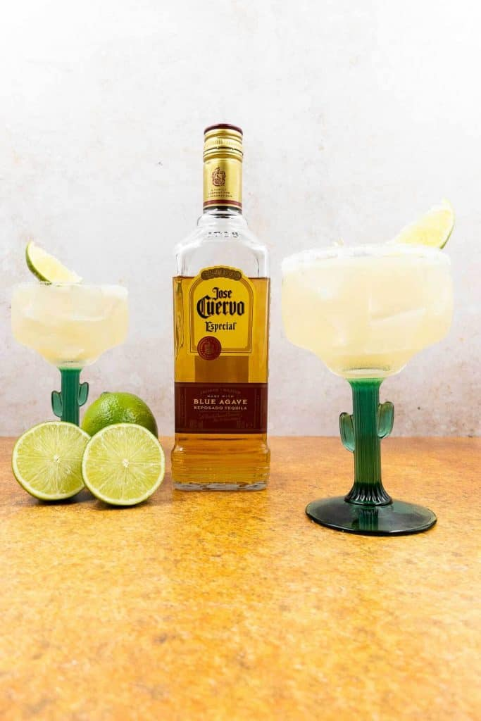 Homemade margarita on the rocks with a bottle of tequila.
