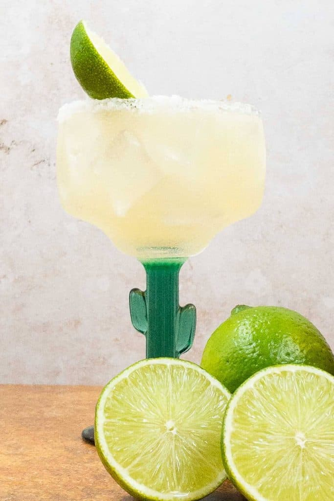 Classic margarita on the rocks in a margarita glass with salted rim and limes surrounding it.