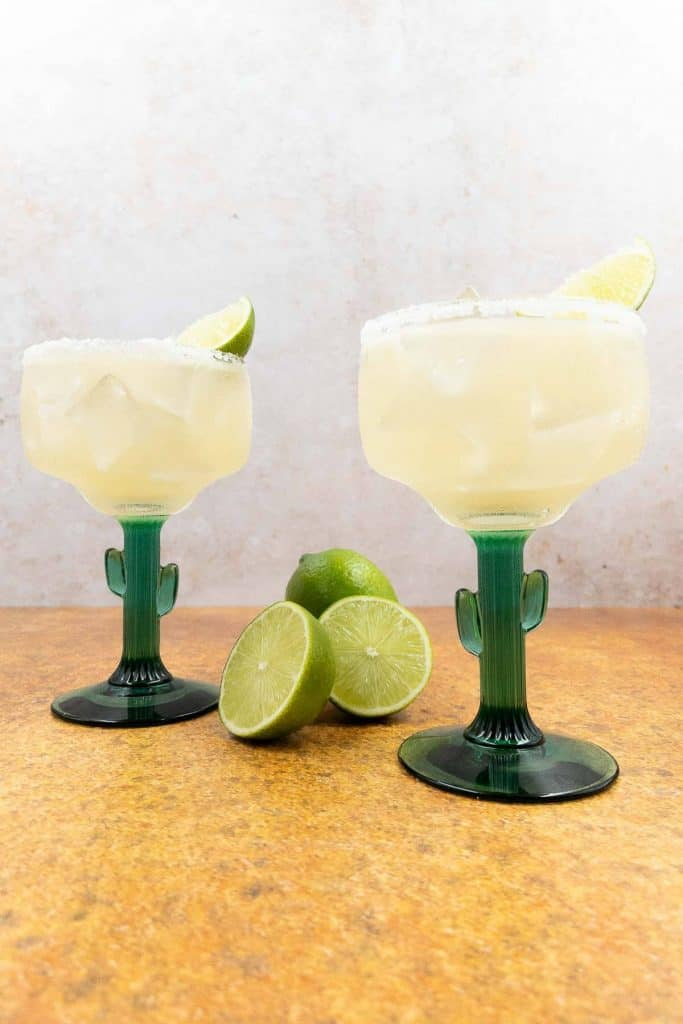 Two classic margaritas, in cactus margarita glasses, with lime wedges.