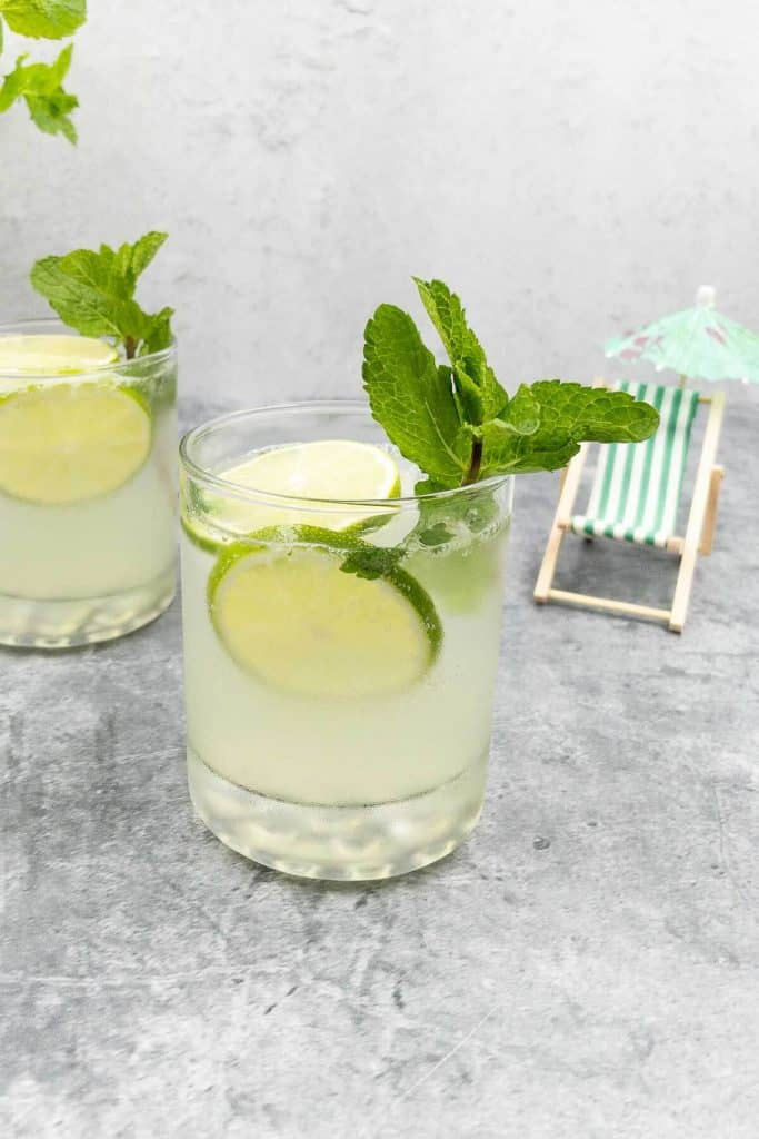 Mojitorita cocktail with lime wheel, mint sprig and a deckchair in the background.