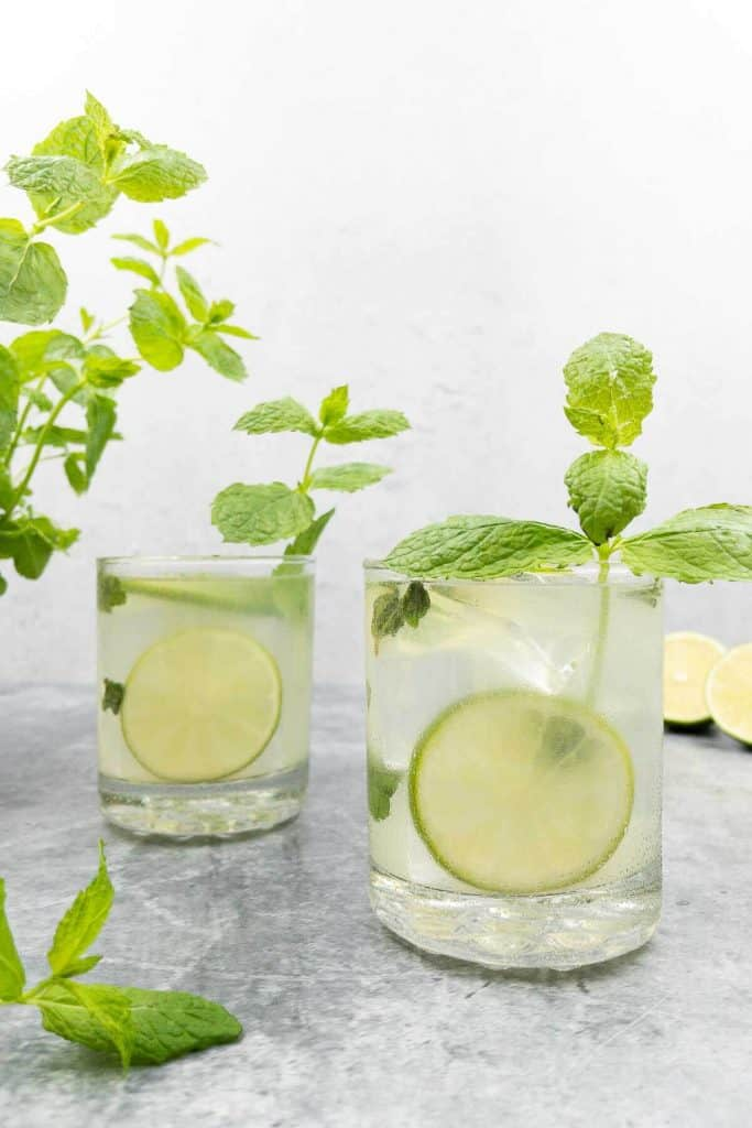 Two mojitoritas in glasses with lime wheels and mint sprigs.