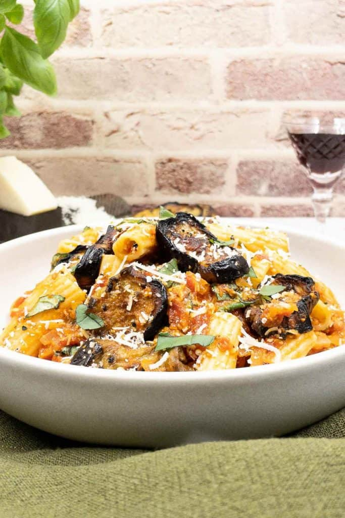 A bowl of pasta à la norma with roasted eggplant, pasta and a glass of Italian red wine.