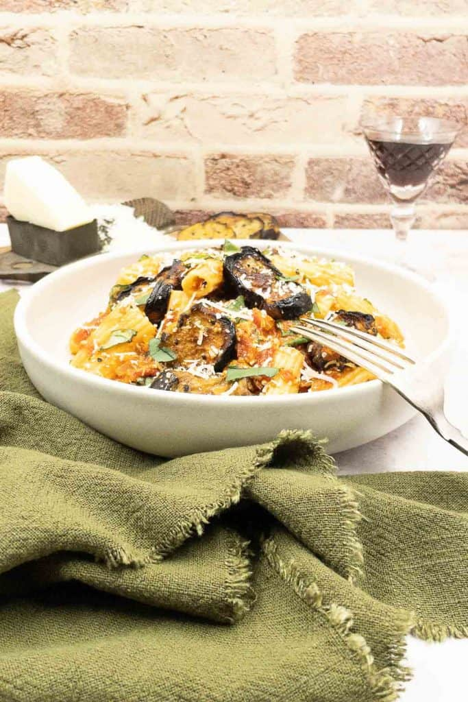 Made from scratch pasta à la norma in a bowl, with roasted eggplant, pasta and cheese, with a fork ready to eat.