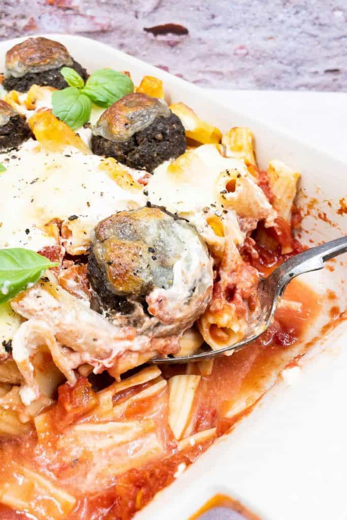 Vegetarian baked pasta in a baking dish, with a serving spoon scooping out rigatoni pasta, tomatoes and a veggie meatball.