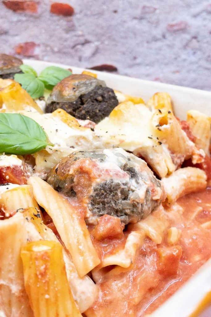 Vegetarian baked pasta in baking dish, with rigatoni pasta, veggie meatballs, mozzarella cheese and tomatoes.