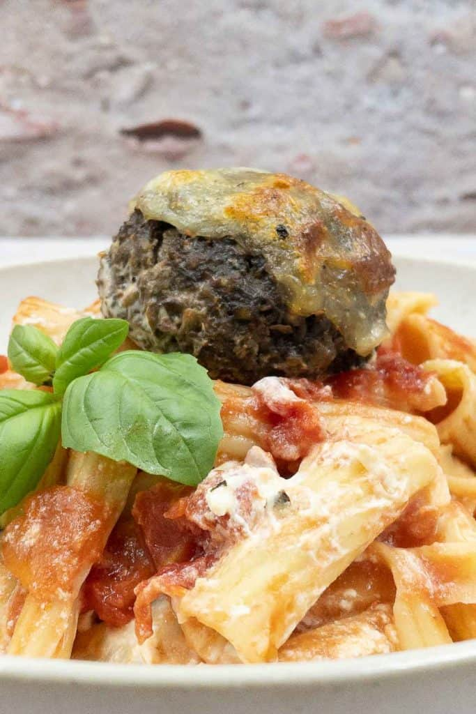 Close up of vegetable pasta bake, with meatless meatball and fresh basil.